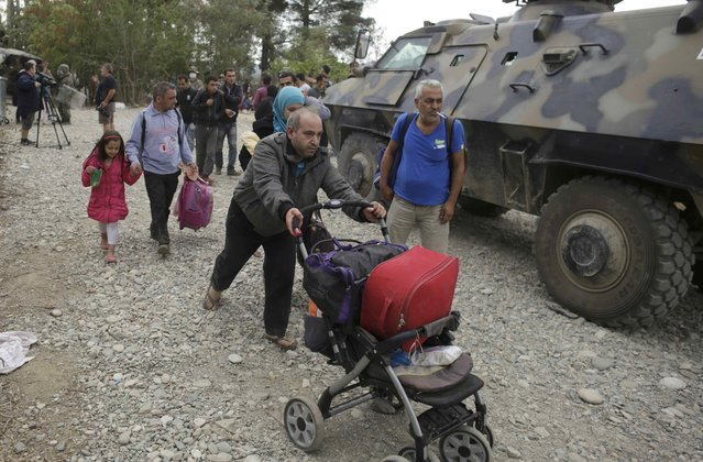 A migrant pushes a pram passed an armoured vehicle of the Macedonian army near Gevgelija, Macedonia, September 7, 2015. (Photo by Stoyan Nenov/Reuters)