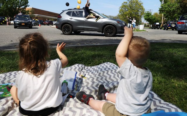 Children wave as graduating Seniors from Wantagh High School drive by the front of the school in a Class of 2020 Parade on May 15, 2020 in Wantagh, New York. In-person learning for the school semester has been cancelled and students will finish their year with online video classes due to the coronavirus COVID-19 pandemic. (Photo by Al Bello/Getty Images)