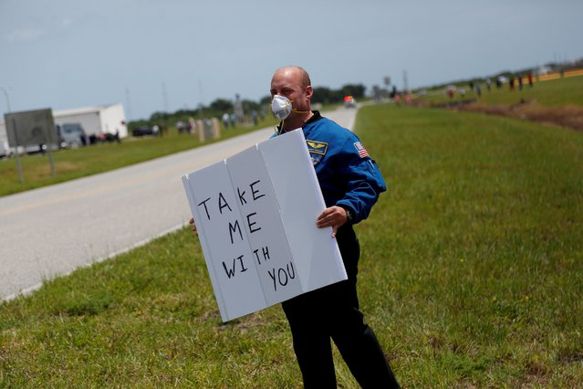 Former NASA astronaut Garrett Reisman holds the sign before the launch of a SpaceX Falcon 9 rocket and Crew Dragon spacecraft at the Kennedy Space Center, in Cape Canaveral, Florida, U.S., May 30, 2020. (Photo by Joey Roulette/Reuters)