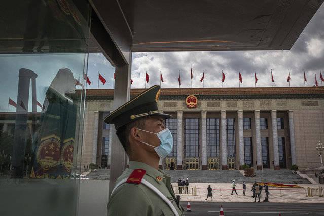 A Chinese People's Liberation Army (PLA) soldier wearing a protective face mask stands guard in front of the Great Hall of the People before the second plenary session of China's National People's Congress (NPC), in Beijing, Monday, May 25, 2020. (Photo by Roman Pilipey/Pool Photo via AP Photo)