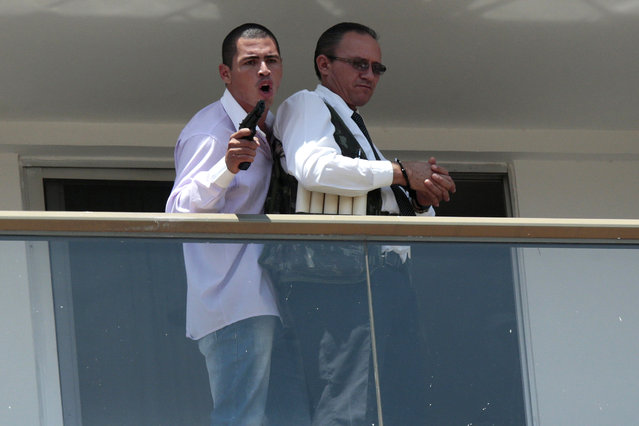 An unidentified man (L) holds a gun after forcing an employee of the Saint Peter Hotel to put on what he claims is a vest loaded with explosives, on a balcony of the hotel in Brasilia, September 29, 2014. According to local media, the man checked into the hotel in the morning and then proceeded to bang on doors and yell for guests to evacuate the hotel, before taking the employee hostage. (Photo by Ueslei Marcelino/Reuters)