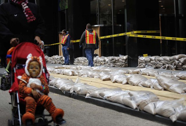 Sandbags are placed in front of No. 2 Broadway in Manhattan's Battery Park on Sunday. (Photo by Louis Lanzano/Associated Press)