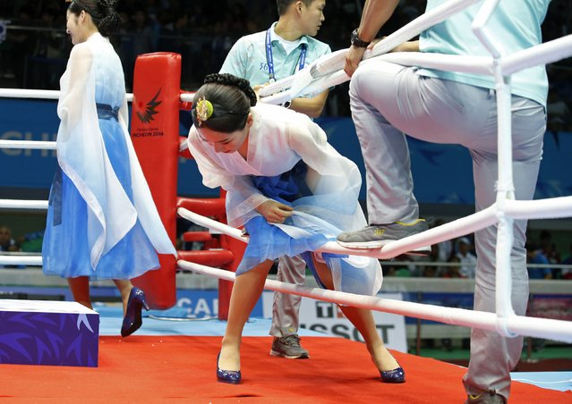 A medal presenter, dressed in a modified Korean tradition garb, climbs into the boxing ring to participate in the awarding of the gold medal to South Korea's Shin Jong-hun, winner of the gold medal in the men's light flyweight -49kg boxing bout at the Seonhak Gymnasium during the 2014 Asian Games in Incheon, October 3, 2014. (Photo by Kim Kyung-Hoon/Reuters)
