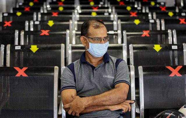 A Sri Lankan man wearing a face mask sits in the waiting area among rows of seats marked with signs abiding to the social distancing guidelines at the Department of Immigration and Emigration building in Colombo, Sri Lanka, 29 May 2020. The Sri Lankan government has started lifting most of the restrictions implemented nearly two months ago in a bid to slow down the spread of the SARS-CoV-2 coronavirus that causes the COVID-19 disease, and is preparing for a full reopening of businesses and activities to avoid an economic slump. (Photo by Chamila Karunarathne/EPA/EFE)