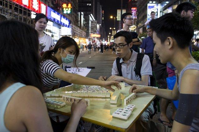 Protesters play mahjong on a main road at the Mongkok shopping district in Hong Kong October 9, 2014. (Photo by Tyrone Siu/Reuters)