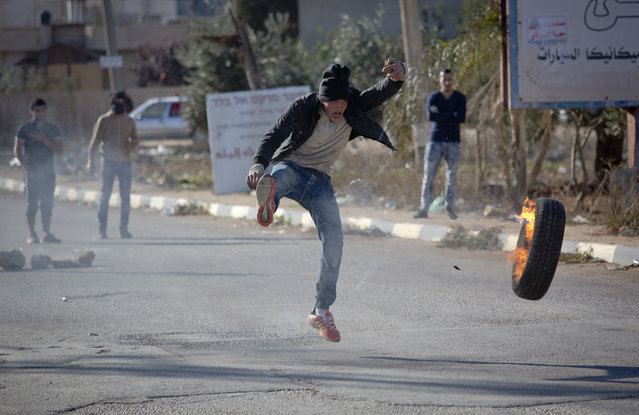 A Palestinian protester kick a tire during clashes with Israeli troops in the village of Qusra, near the West Bank City of Nablus, Thursday, November 30, 2017, after a Jewish West Bank settler fatally shot a 47-year-old Palestinian villager in a clash that occurred under disputed circumstances. (Photo by Majdi Mohammed/AP Photo)