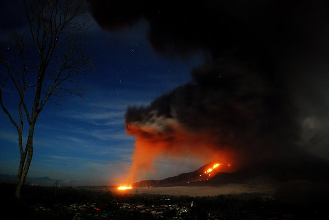 This long exposure photograph taken late on October 9, 2014 shows scorching lava flow and giant ash clouds released from the crater during the eruption of Mount Sinabung volcano as seen from Karo district located in Sumatra island. Indonesian authorities said pyroclastics flow reached 4.5 kilometers down the slope threatening populated villages whlie ash clouds reached three kilometers to the sky during it latest series of eruption that began on October 5. (Photo by Sutanta Aditya/AFP Photo)
