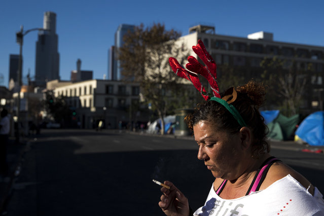 "Wearing a Christmas headband, Grace Fernandez, who is homeless, smokes outside her tent in the Skid Row area of downtown Los Angeles, Friday, December 1, 2017. ""Holidays are just so much special. It should bring us altogether as one even if we are homeless"", said Fernandez. (Photo by Jae C. Hong/AP Photo)"