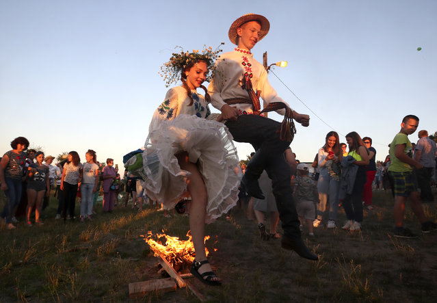 People in ethnic costumes jump over a bonfire during Ivan Kupala Day celebrations held by the Pripyat River in the town of Turauin Gomel Region, Belarus on July 6, 2020. Ivan Kupala Day, also known as Ivana-Kupala or Kupala Night, is a traditional pagan holiday celebrated in eastern Slavic cultures. Various rituals are traditionally performed on Kupala Night, including making flower wreaths, fortune-telling, jumping over bonfires, and burning a wheel-like effigy symbolizing the sun. (Photo by Natalia Fedosenko/TASS)