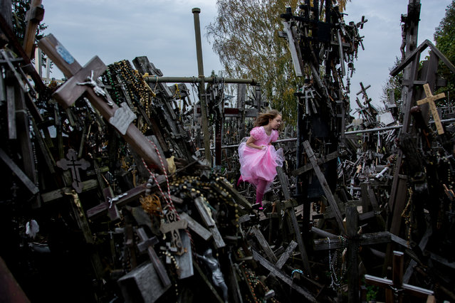 """Cross and Girl"". A girl ran through the hill of cross. Photo location: Siauliai, Lithuania. (Photo and caption by Hideki Mizuta/National Geographic Photo Contest)"