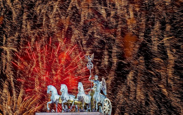 Fireworks explode above the Quadriga on the Brandenburg Gate during celebrations in Berlin. (Photo by Markus Schreiber/Associated Press)