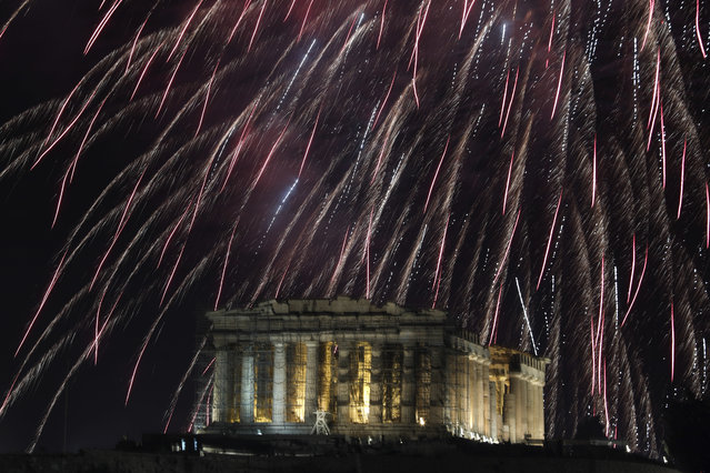 Fireworks explode over the temple of the Parthenon at the Acropolis hill to mark the New Year's celebrations in Athens, Greece, Monday, January 1, 2018. (Photo by Yorgos Karahalis/AP Photo)