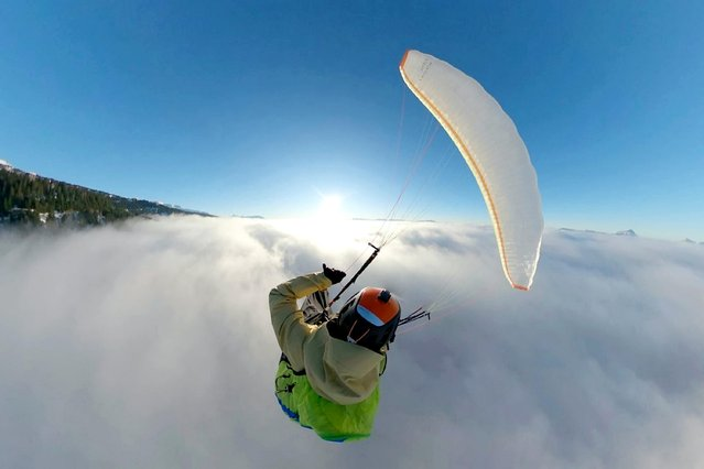 The photo shows 31-year-old film-maker Etienne Mérel captured himself soaring through the clouds on a paraglider above his base in the mountains of Grenoble, France on July 9, 2020. (Photo by Etienne Merel/South West News Service)
