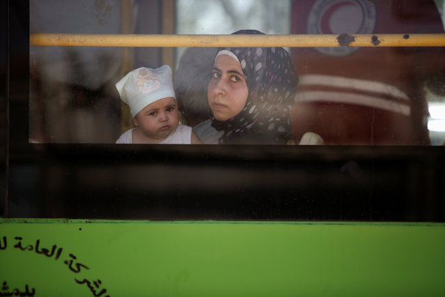 A woman and a child ride a bus in Daraya while being evacuated, after reports of an agreement between rebels and Syria's army to evacuate civilians and rebel fighters from Moadamiya, in Damascus, Syria September 2, 2016. (Photo by Omar Sanadiki/Reuters)