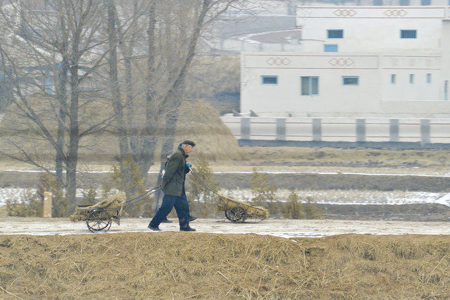 A local resident pushes and pulls a load in February, 2013, in the Demilitarised Zone, North Korea. (Photo by Andrew Macleod/Barcroft Media)