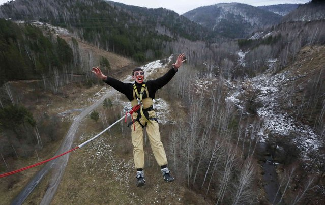 """A member of the amateur rope-jumping group """"Exit Point"""" wears Halloween make-up as he jumps from a 44-metre high (144-ft) water pipe bridge in the Siberian Taiga area outside Krasnoyarsk, November 2, 2014. (Photo by Ilya Naymushin/Reuters)"""