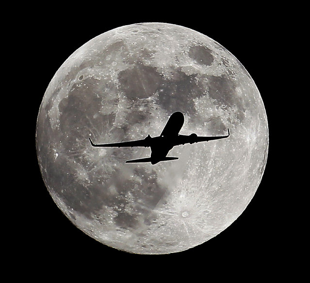 A passenger airliner crosses the full moon, also known as the Hunter's Moon, a few hours prior to the beginning of a total lunar eclipse that will create an effect known as the Blood Moon, in Whittier, Ca., on Tuesday evening, October 7,  2014. (Photo by Nick Ut/AP Photo)