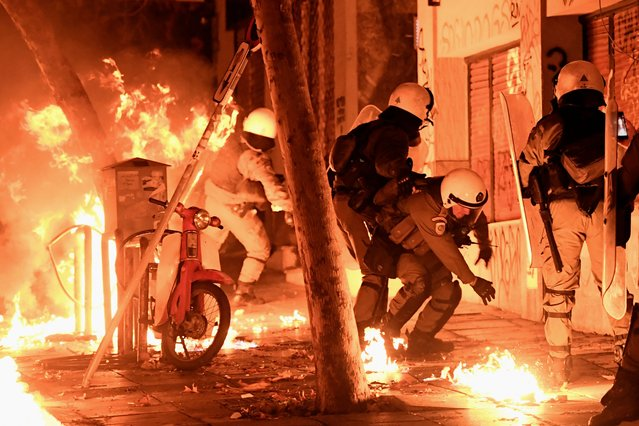 A petrol bomb explodes next to anti-riot policemen in downtown Athens on November 17, 2017, during clashes following a rally commemorating the 1973 students uprising against the US-backed military junta. Thousands marched in Greece on November 17, amid tight security, to commemorate a student uprising that helped bring down a US-backed junta in 1974. (Photo by Aris Messinis/AFP Photo)