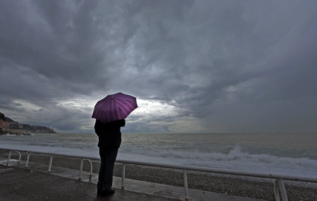 A woman protects herself under an umbrella during an autumn day on the Promenade Des Anglais in Nice while heavy rain and storm hit the French Riviera November 5, 2014. (Photo by Eric Gaillard/Reuters)