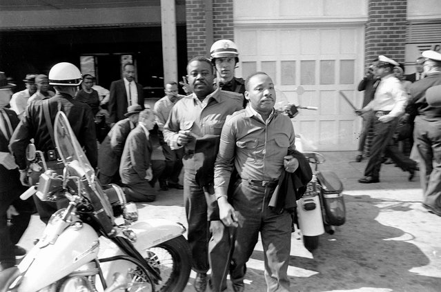 Rev. Ralph Abernathy, left, and Rev. Martin Luther King Jr., are removed by a policeman as they led a line of demonstrators into the business section of Birmingham, Alabama, on April 12, 1963. (Photo by AP Photo)