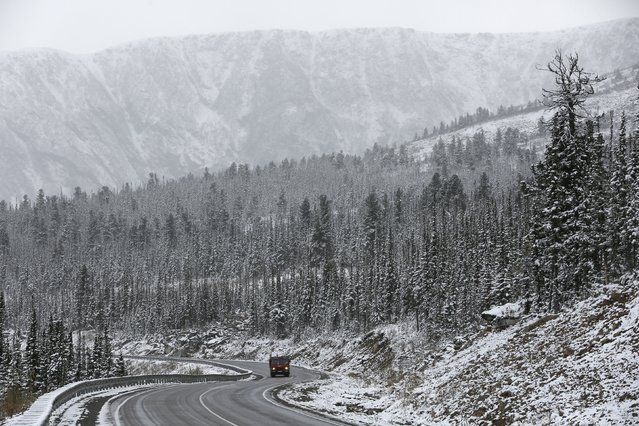 """A truck drives along the M54 """"Yenisei"""" highway during a snowfall in the Western Sayan mountains in Southern Siberia near an administrative border with Tuva region, Russia, October 6, 2015. (Photo by Ilya Naymushin/Reuters)"""