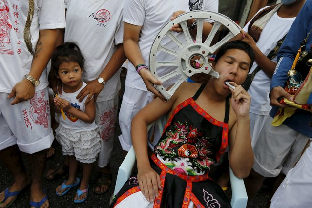 A devotee of the Chinese Bang Neow shrine with a piece of a car wheel pierced through his cheek pauses during a procession celebrating the annual vegetarian festival in Phuket, Thailand October 18, 2015. (Photo by Jorge Silva/Reuters)