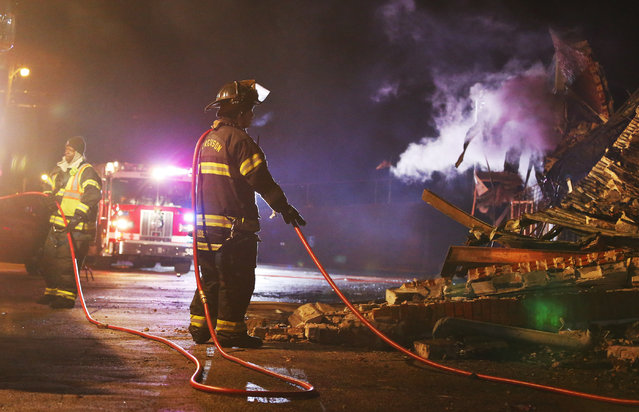 Firefighters work to put out a fire at a business after protesters burned buildings in protest against the Grand Jury decision not to indict a police officer in the shooting death of Michael Brown, in Ferguson, Missouri, USA, 25 November 2014. (Photo by Larry W. Smith/EPA)