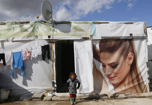A Syrian refugee girl stands near her tent at a refugee camp in Zahle in the Bekaa valley November 27, 2014. (Photo by Jamal Saidi/Reuters)