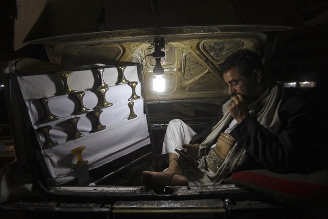 A vendor selling the janbiya, a traditional dagger, looks at his handphone by the light of a lamp as he displays his wares for customers, at the back of his car at a marketplace in the Old City of Sanaa November 23, 2014. (Photo by Mohamed al-Sayaghi/Reuters)
