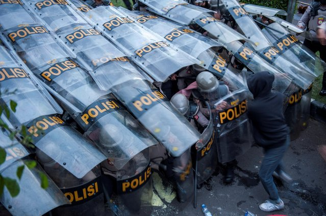 """A demonstrator clashes with a barricade of police officers during a protest against the government's proposed labor reforms outside the Regional Parliament building in Bandung, West Java province, Indonesia, October 6, 2020. The """"omnibus"""" jobs creation bill has seen thousands of people across the world's fourth-most populous nation take to the streets in protest against legislation they say undermines labor rights and weakens environmental protections. (Photo by Arie Nugraha/Antara Foto via Reuters)"""