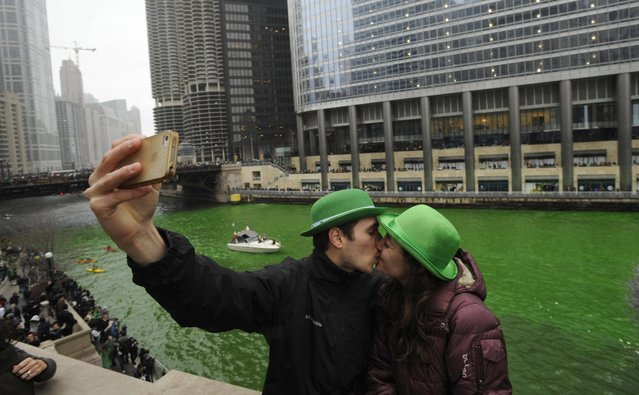 John Shepard and Gena Damento of Rochester Minn., take a photo of themselves kissing after the Chicago River was dyed green ahead of the St. Patrick's Day parade in Chicago, Saturday, March, 16, 2013.  With the holiday itself falling on a Sunday, many celebrations were scheduled instead for Saturday because of religious observances. (Photo by Paul Beaty/AP Photo)
