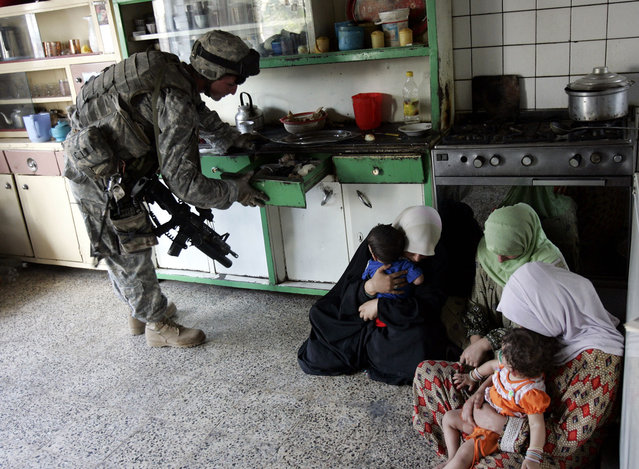 A U.S. soldier from Alpha company 1-17 regiment of the 172th brigade searches a house as women and children look on, in eastern Baghdad, on October 3, 2006. The U.S military has been performing scout missions aimed at preparing security operations to stop sectarian violence in the capital. (Photo by Darko Bandic/AP Photo/The Atlantic)