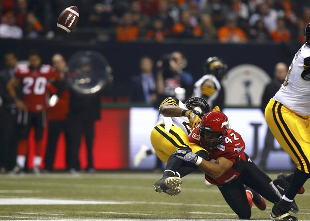 Hamilton Tiger Cats' Nic Grigsby (L) fumbles the ball as he is hit by Calgary Stampeders' Deron Mayo in the first half during the CFL's 102nd Grey Cup football championship in Vancouver, British Columbia, November 30, 2014. (Photo by Mark Blinch/Reuters)