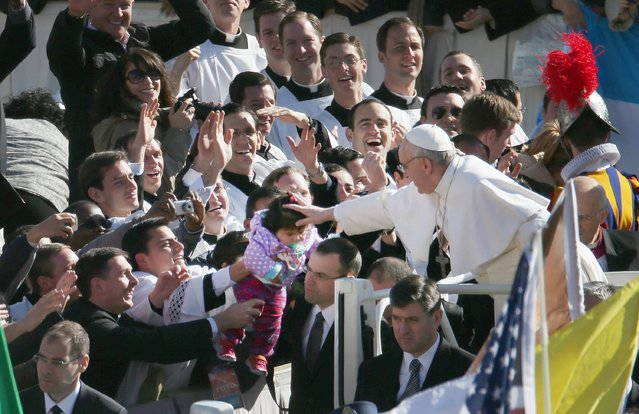 Pope Francis touches a child's head as he arrives in the Pope Mobile for his Inauguration Mass in St Peter's Square on March 19, 2013 in Vatican City, Vatican. The mass is being held in front of an expected crowd of up to one million pilgrims and faithful who have filled the square and the surrounding streets to see the former Cardinal of Buenos Aires officially take up his role as pontiff. Pope Francis' inauguration takes place in front of Cardinals and spiritual leaders as well as heads of state from around the world. (Photo by Peter Macdiarmid)