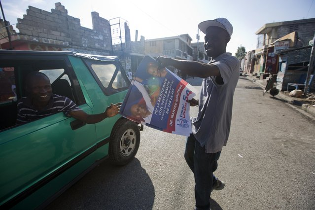 A supporter of Maryse Narcisse gives out campaign posters promoting the presidential candidate, in Port-au-Prince, Haiti, Tuesday, August 23, 2016. Campaign season begins yet again for Haiti as authorities organize a redo of last year's presidential vote. (Photo by Dieu Nalio Chery/AP Photo)