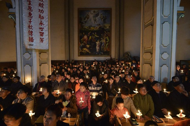 Worshippers hold candles during a mass on the eve of Easter, at a catholic church in Taiyuan, Shanxi province of China, on March 30, 2013. (Photo by Jon Woo/Reuters)