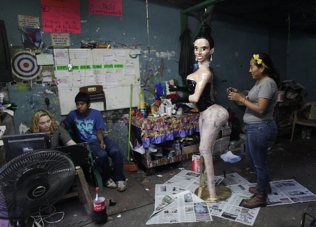 Adriana Ramirez (R) works on the outfit for a pinata depicting TV celebrity Kim Kardashian at her brother's workshop in Reynosa December 6, 2014. (Photo by Daniel Becerril/Reuters)