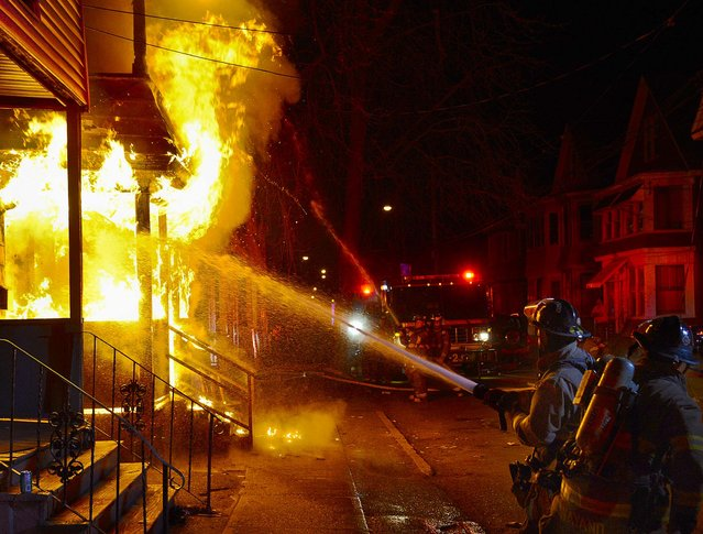 Schenectady firefighters battle a 2-alarm fire that left 2 families homeless in New York, on April 7, 2013. One resident was taken by ambulance to a local hospital for smoke inhalation. (Photo by Peter R. Barber/The Daily Gazette)