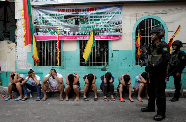 Members of the police SWAT team stand guard near residents who were rounded up, after police sources and local media reported that people were killed during a drug raid, in Manila, Philippines, October 7, 2016. (Photo by Czar Dancel/Reuters)
