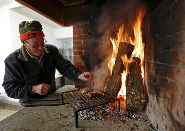 Goffredo Guidotti grilles some bacon and sausage in the squad hunting-house before to go for an hunt in Castell'Azzara, Tuscany, central Italy, November 1, 2015. (Photo by Max Rossi/Reuters)