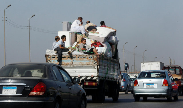 Egyptian people ride with their luggage on a truck at the agricultural road which leads to the capital city of Cairo, Egypt, October 13, 2016. (Photo by Amr Abdallah Dalsh/Reuters)