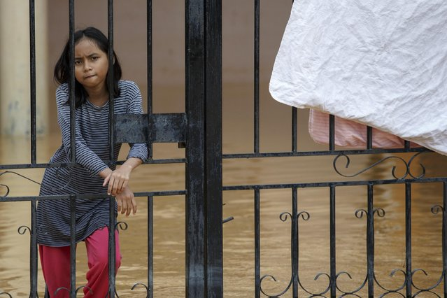 A girl looks from her flooded house on the outskirt of Kota Bharu in Kelantan December 29, 2014. The worst flooding in Malaysia in more than a decade has killed 10 people and forced nearly 160,000 from their homes and more rain is expected, authorities said on Sunday. (Photo by Athit Perawongmetha/Reuters)
