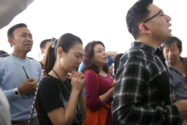 Relatives of the crashed AirAsia plane passengers pray at Juanda Airport, in Surabaya, Indonesia, 31 December 2014epa04543267