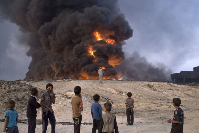 in Qayyarah, about 31 miles (50 km) south of Mosul, Iraq, Sunday, October 23, 2016.in Qayyarah, some 50 kilometers south of Mosul, Iraq, Sunday, Oct. 23, 2016. Islamic State fighters torched a sulfur plant south of Mosul, sending a cloud of toxic fumes into the air that mingled with oil wells the militants had lit on fire to create a smoke screen. (Photo by Marko Drobnjakovic/AP Photo)