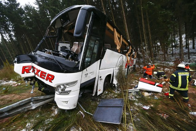 Firefighters work on the site of a bus crash on a slope next to the A4 motorway near the town of Bad Hersfeld, December 30, 2014. (Photo by Ralph Orlowski/Reuters)