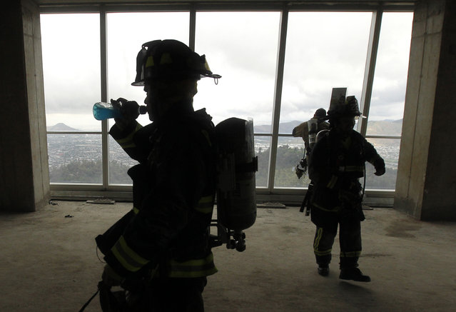 """Firefighters are pictured after climbing the 1800 steps of the Costanera Centre Tower as part of the """"Race for Life"""" aimed at encouraging organ donation in Chile, in Santiago, on October 16, 2016. (Photo by Claudio Reyes/AFP Photo)"""