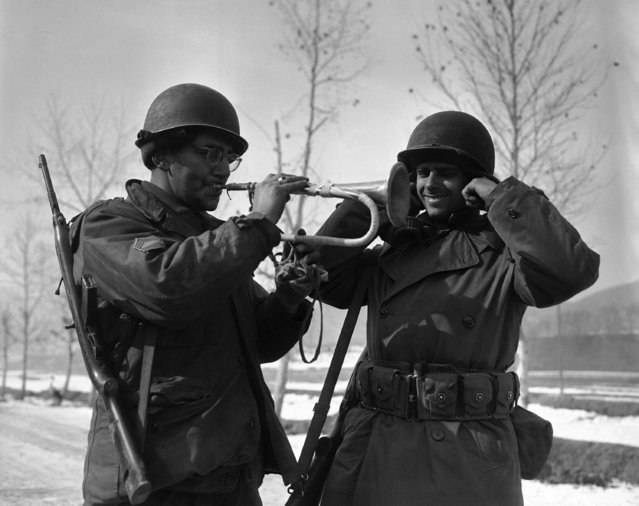 Sgt. Tony J. Fruio, El Paso, Tex., blows a sour note on a Chinese bugle to the intense discomfort of his buddy, Cpl. Hugh Cole (right) of St. Charles, Ill. on February 2, 1951. The bugle, picked up in an enemy position near Yangji, of west-central Korean front, is type used by the Chinese troops during attack. (Photo by Max Desfor/AP Photo)