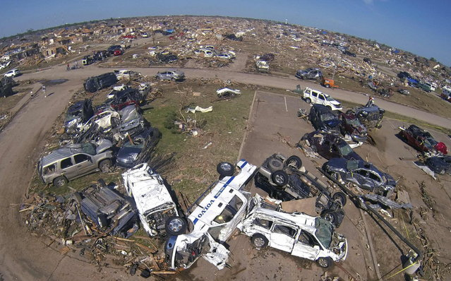 A pile of destroyed cars of teachers sits outside Briarwood elementary school in Oklahoma City, Oklahoma May 22, 2013.  Rescue workers with sniffer dogs picked through the ruins on Wednesday to ensure no survivors remained buried after a deadly tornado left thousands homeless and trying to salvage what was left of their belongings. Curvature of horizon in the photo is due to an ultra-wide angle lens. (Photo by Rick Wilking/Reuters)