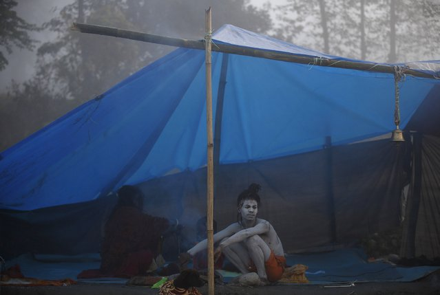 "A Hindu holy man or ""Sadhu"" sits near a fire to keep himself warm on the first day of Swasthani Brata Katha festival in Kathmandu January 5, 2015. (Photo by Navesh Chitrakar/Reuters)"
