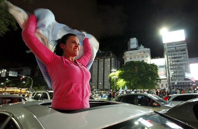 A supporter of presidential candidate Mauricio Macri of Cambiemos (Let's Change) waves an Argentine national flag as she celebrates in Buenos Aires November 22, 2015. Conservative opposition challenger Macri won Argentina's presidential election on Sunday, bringing to an end more than a decade of free-spending leftist populism with a promise to open up the ailing economy to investors. (Photo by Martin Acosta/Reuters)